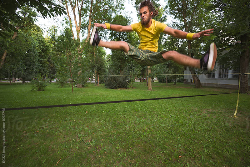 Young man in motion jumping on a slackline by RG&B Images for Stocksy United