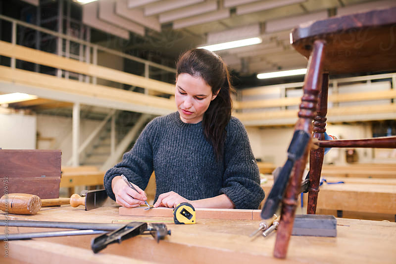 Female woodworker working concentrated behind a bench  by Ivo de Bruijn for Stocksy United