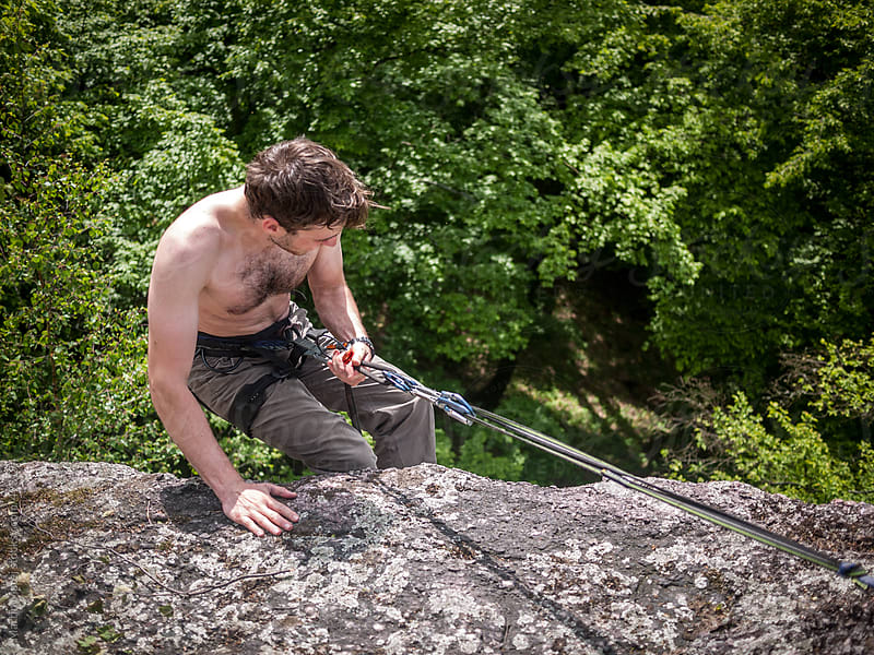 Half naked climber rapelling down from rock by Martin Matej for Stocksy United