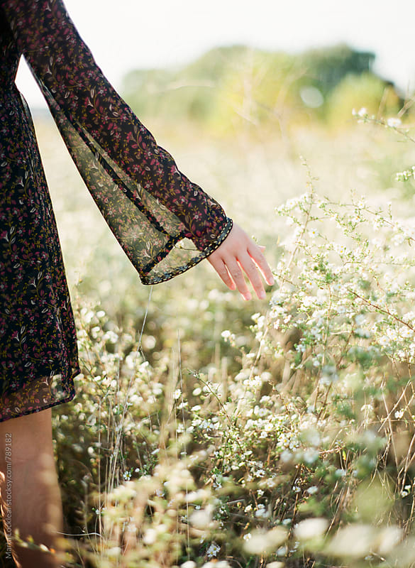 A girl and a field of wildflowers by Marta Locklear for Stocksy United