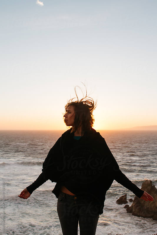 lifestyle image of young female woman exploring windy coast pacific ocean by Jesse Morrow for Stocksy United