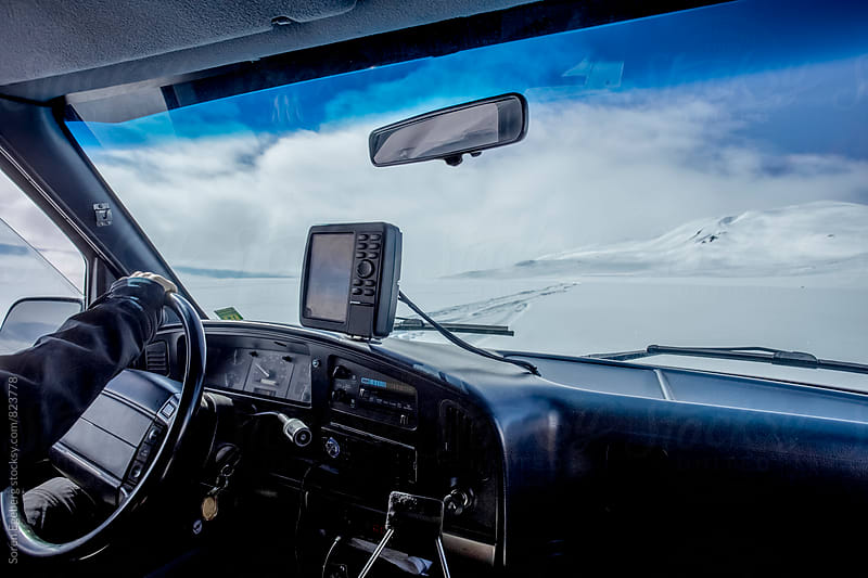 Dashboard with GPS in 4WD vehicle driving in snowy landscape by Soren Egeberg for Stocksy United