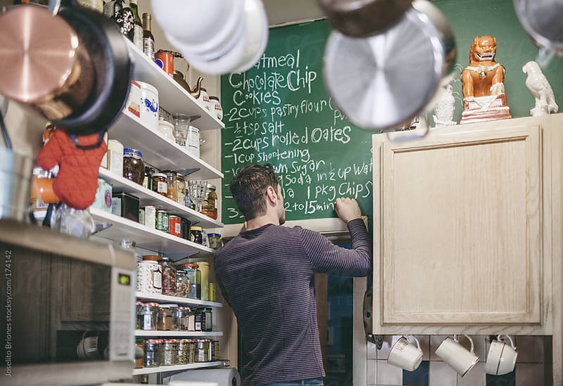 Man Writing Mom's Recipe of his Favorite Cookie on Chalkboard in Small but Organized Kitchen by Joselito Briones for Stocksy United