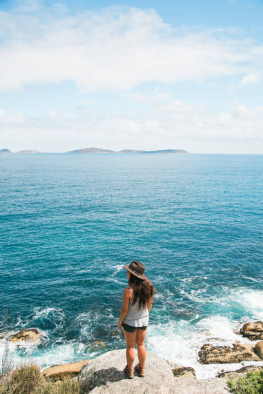 A girl wearing a hat stands on a cliff overlooking the blue ocean by Gary Parker for Stocksy United