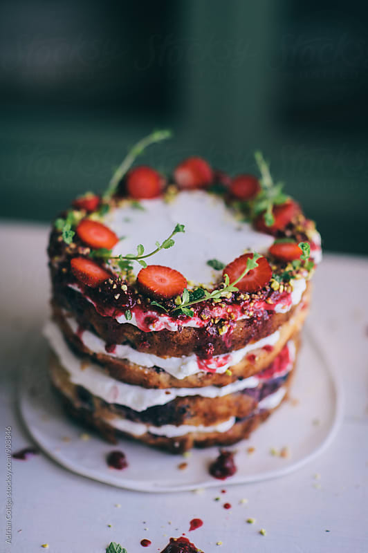 Delicious cake; naked cake with strawberries decorated with mint leaves by Adrian Cotiga for Stocksy United