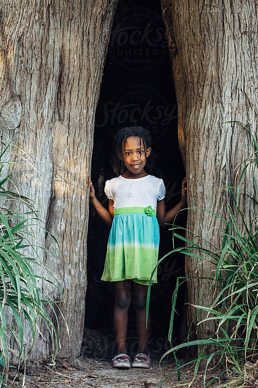 Cute black girl in a tree hollow by Gabriel (Gabi) Bucataru for Stocksy United