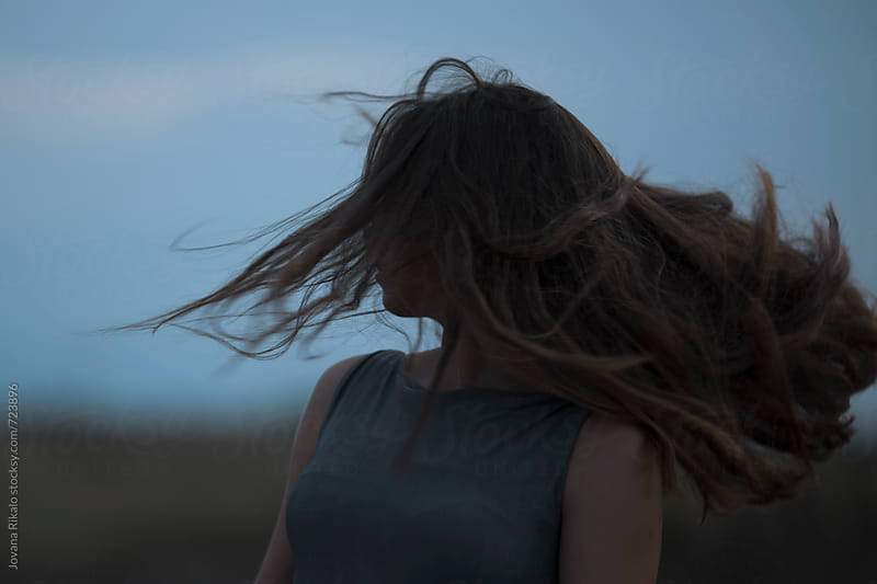 Portrait of a young woman with wind in her hair by Jovana Rikalo for Stocksy United