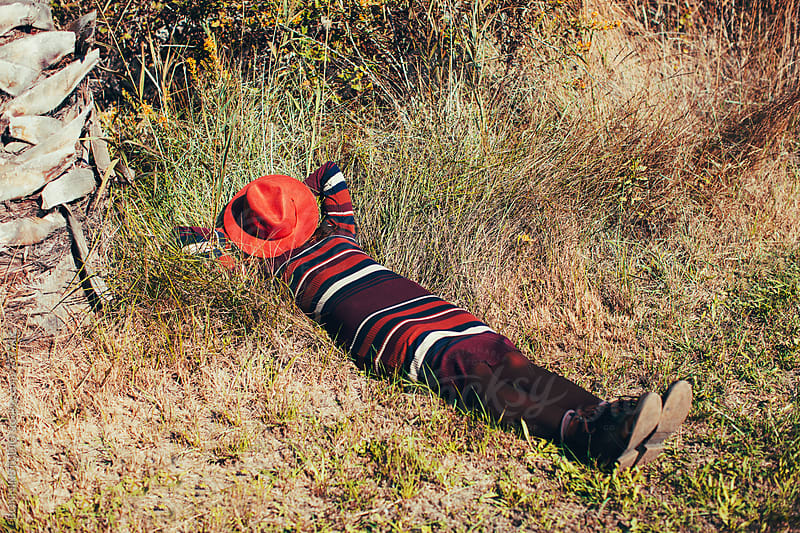 Anonymous woman hiding her face with a hat lying on the grass. by BONNINSTUDIO for Stocksy United