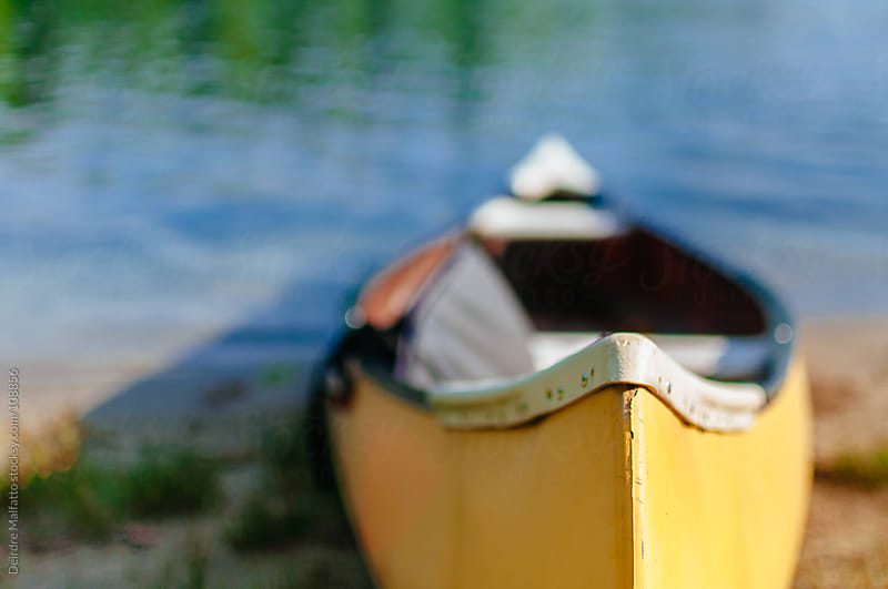 yellow canoe on a blue lake by Deirdre Malfatto for Stocksy United