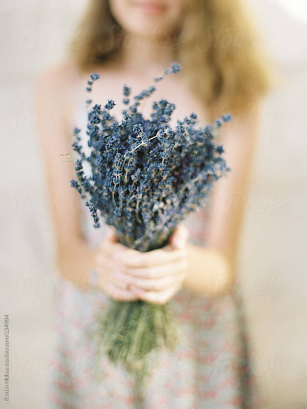 Girl holding posey of lavender by Kirstin Mckee for Stocksy United