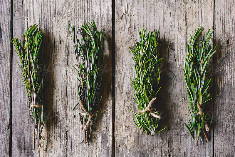 Rosemary herb bundles on wooden table by Pixel Stories for Stocksy United