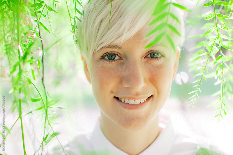 Portrait of a smiling woman between green leaves. by BONNINSTUDIO for Stocksy United