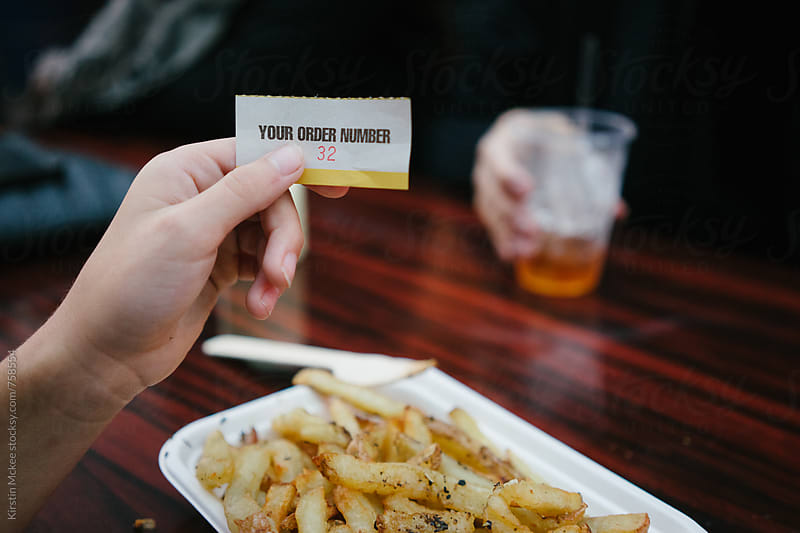 Holding up a ticket for food at a London pop up by Kirstin Mckee for Stocksy United