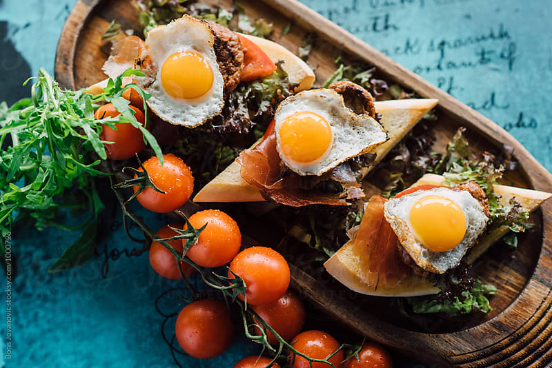 Tasty mini burgers with quail eggs on the top and cherry tomato as decoration by Boris Jovanovic for Stocksy United