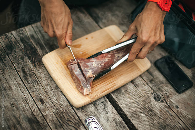 Cutting a steak on a picnic table while camping by Kristine Weilert for Stocksy United