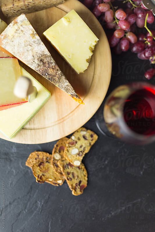Cheese board with crackers overhead by Kirsty Begg for Stocksy United