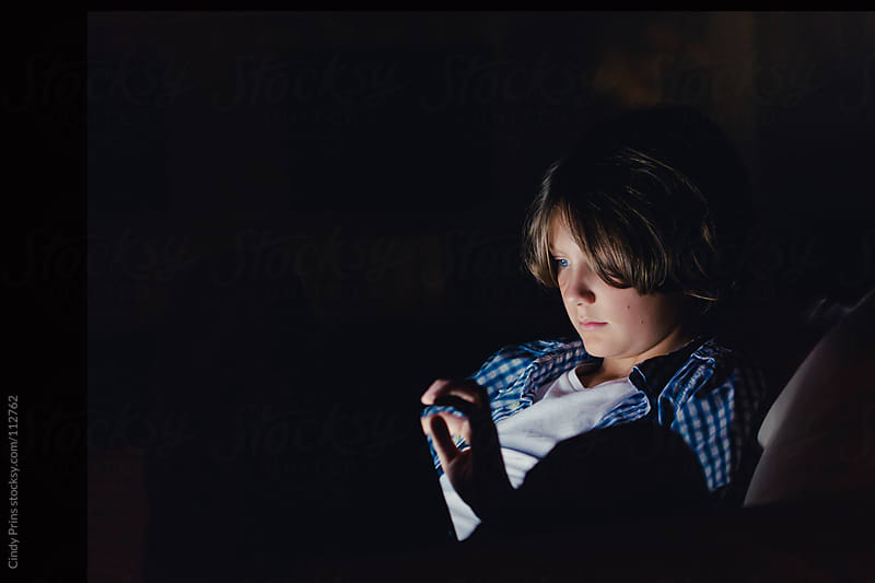 Boy sitting in the dark playing a game on a tablet by Cindy Prins for Stocksy United