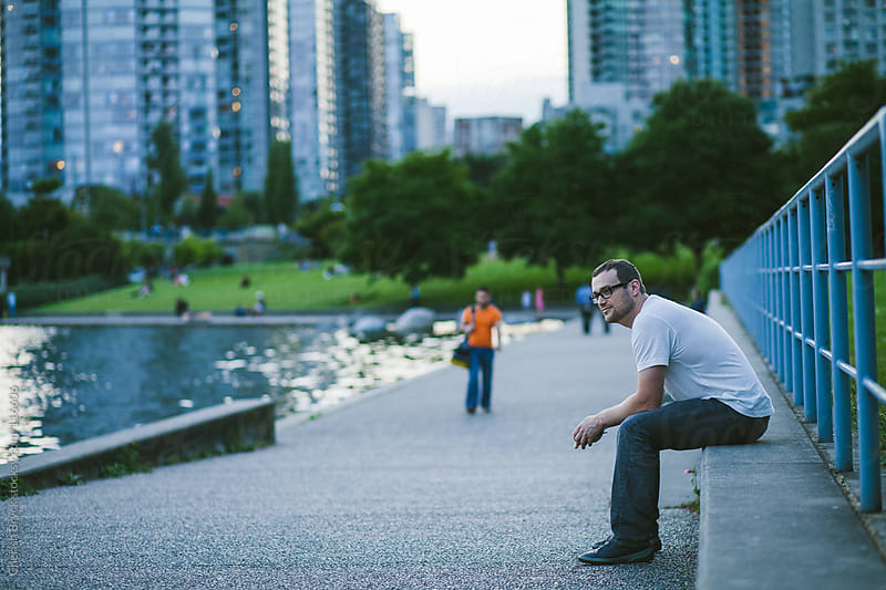 Man sits in city centre near the water. by Cherish Bryck for Stocksy United