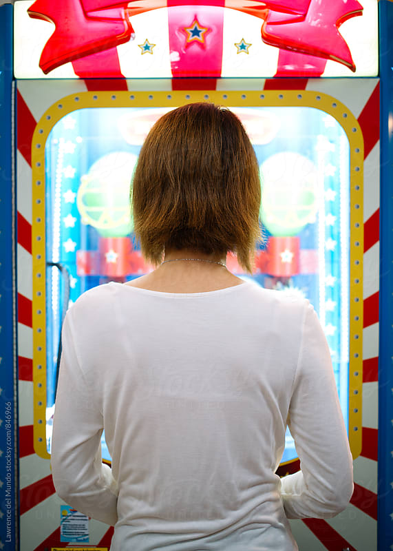 Back view of a lady playing an arcade game  by Lawrence del Mundo for Stocksy United