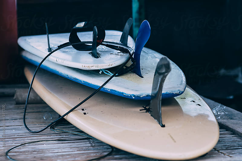 Stack of surfboards with fins and leash  by Soren Egeberg for Stocksy United