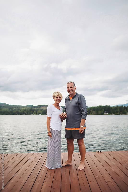Mature couple looking at camera near lake holding hands by Rob and Julia Campbell for Stocksy United