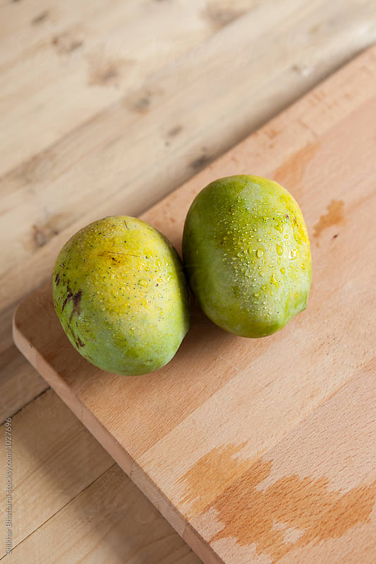 Fresh mangoes on a cutting board. by Shikhar Bhattarai for Stocksy United