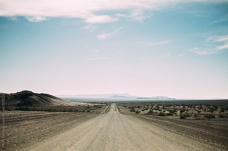 Long empty desert road heading into the horizon by Micky Wiswedel for Stocksy United