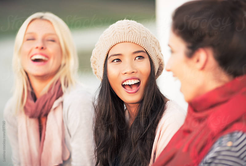 Smiling Women Chatting Outdoors by Lumina for Stocksy United