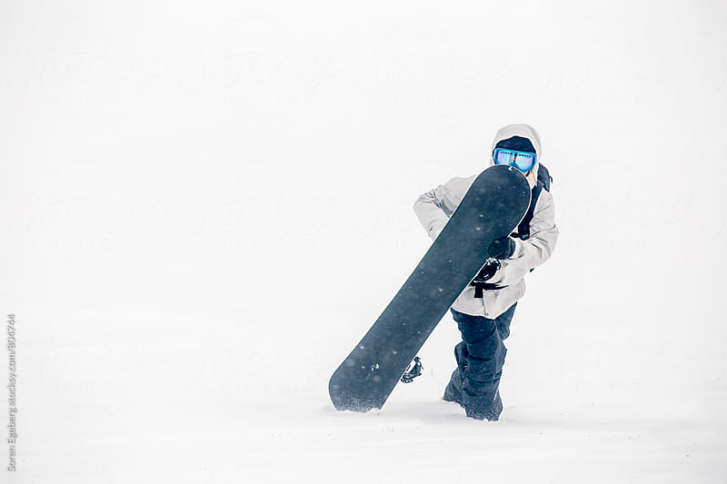 Female snowboarder walking in the snow with snowboard by Soren Egeberg for Stocksy United