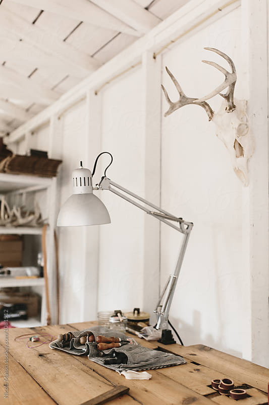 lamp on table in workspace  by Nicole Mason for Stocksy United