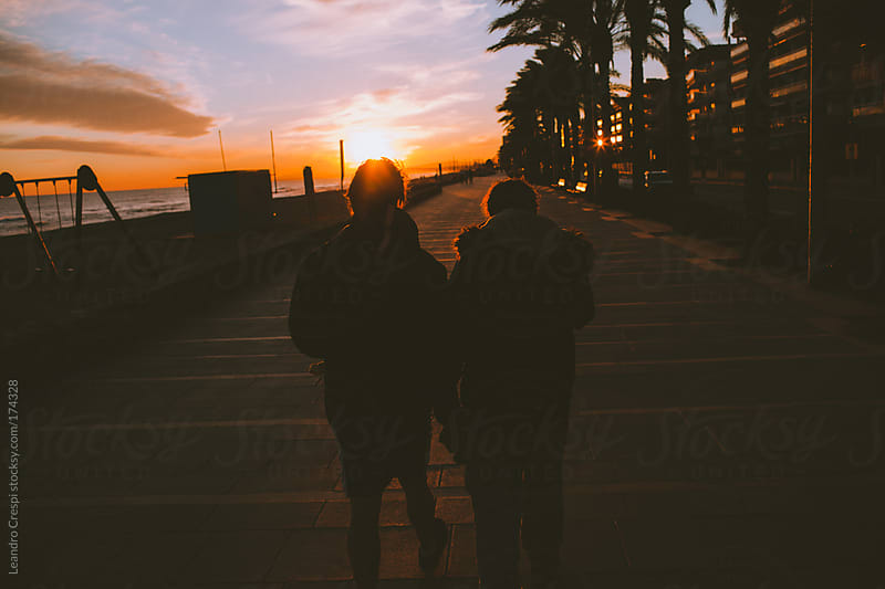 Male's couple walking from behind on sunset by Leandro Crespi for Stocksy United