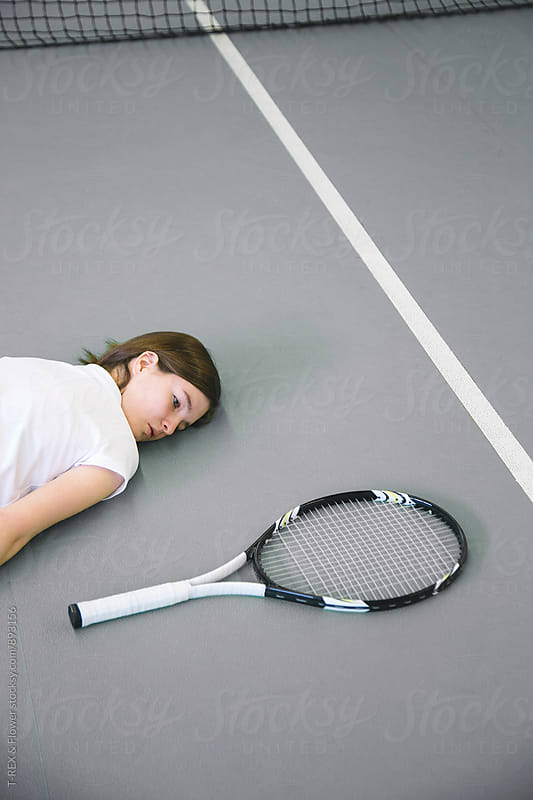 Girl lying on floor while looking at tennis racket by Danil Nevsky for Stocksy United