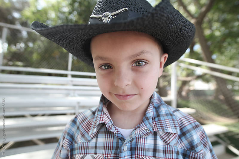 Handsome young cowboy wearing hat and plaid shirt by Dina Giangregorio for Stocksy United