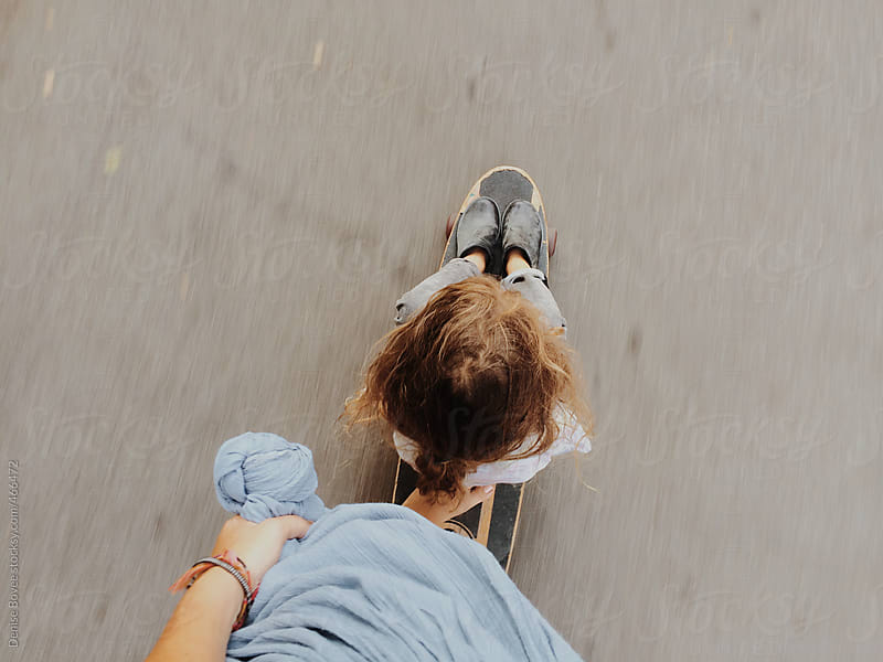 Longboarding Barefoot with Child by Denise Bovee for Stocksy United