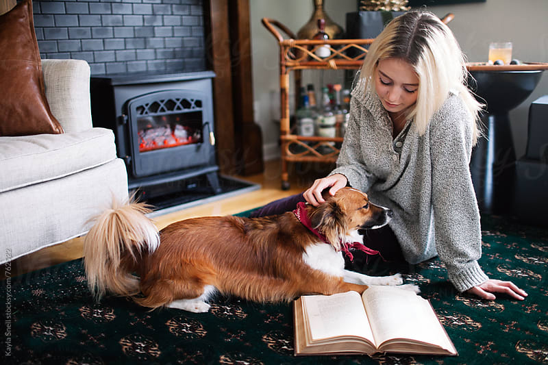 Woman playing with her dog while reading by Kayla Snell for Stocksy United