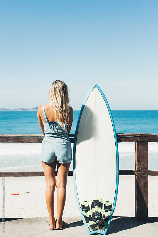 Blond Female Surfer Girl Standing Next to Surfboard on Ipanema Beach in Rio de Janeiro by VISUALSPECTRUM for Stocksy United