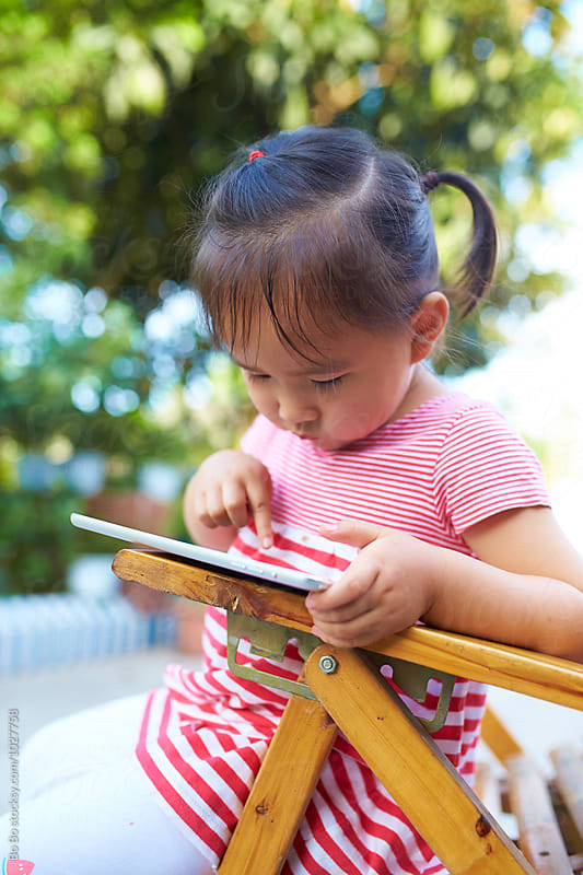 little asian girl playing with tablet in the garden by Bo Bo for Stocksy United
