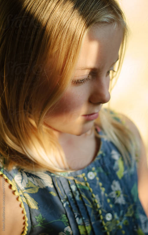 A little girl in a patch of sunlight looking thoughtful by Helen Rushbrook for Stocksy United