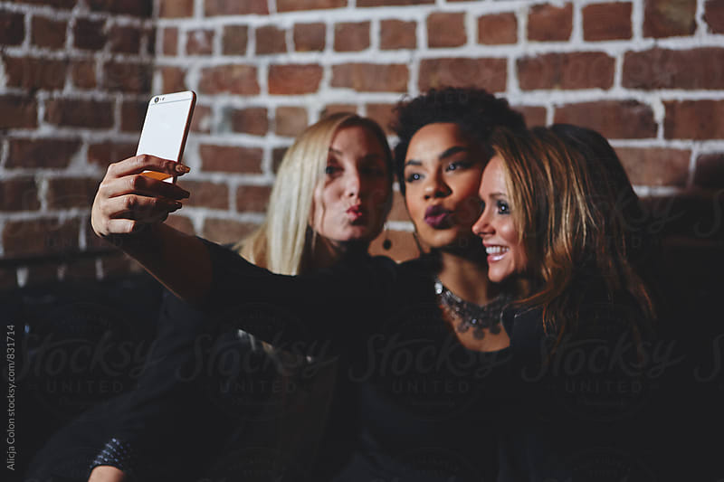 Cute ladies taking a selfie at a lounge by Alicja Colon for Stocksy United