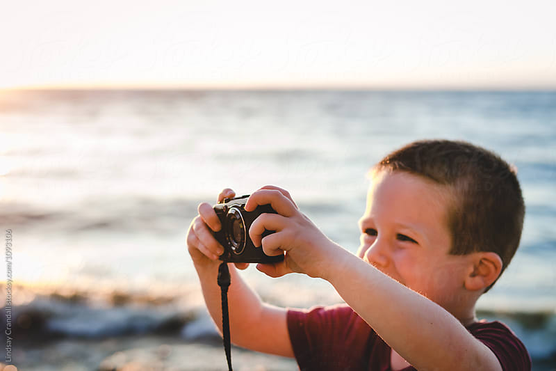 Young boy taking digital photos by a lake by Lindsay Crandall for Stocksy United