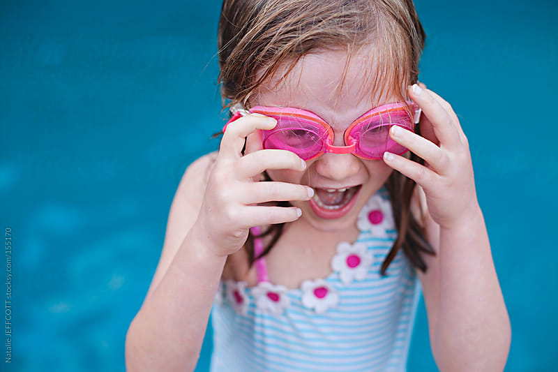 A young girl is excited to jump into a swimming pool in summer by Natalie JEFFCOTT for Stocksy United