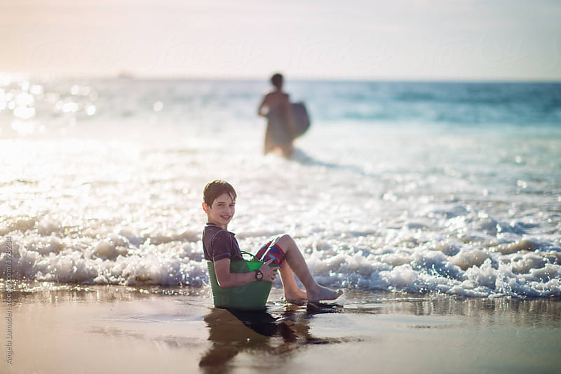 Boy sitting in a green bucket at the beach by Angela Lumsden for Stocksy United