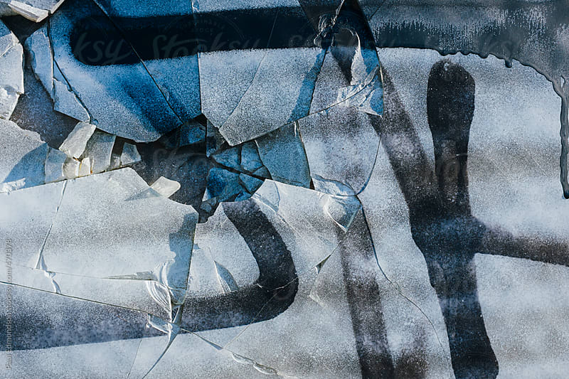 Spray painted graffiti on broken glass window of building exterior, close up by Paul Edmondson for Stocksy United