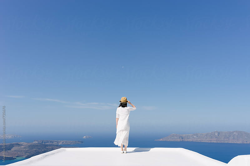 Beautiful chinese girl standing on a platform of Santorini by Maa Hoo for Stocksy United