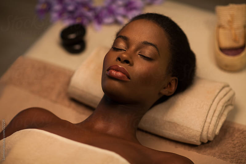 African Woman Lying on a Massage Table by Lumina for Stocksy United