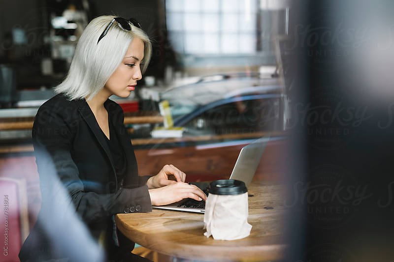 Cool businesswoman sitting at cafe by Simone Becchetti for Stocksy United