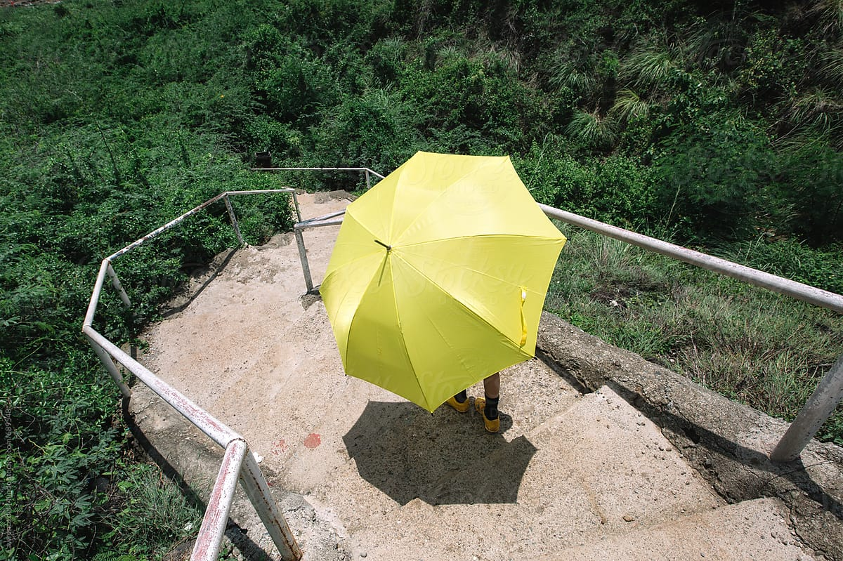 Kid With A Yellow Umbrella Goes Down A Flight Of Stairs Into The Lush Green Below