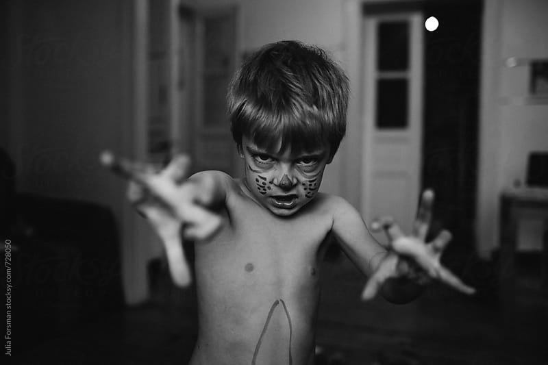 Young boy who has drawn on himself pretends to be a monster. by Julia Forsman for Stocksy United