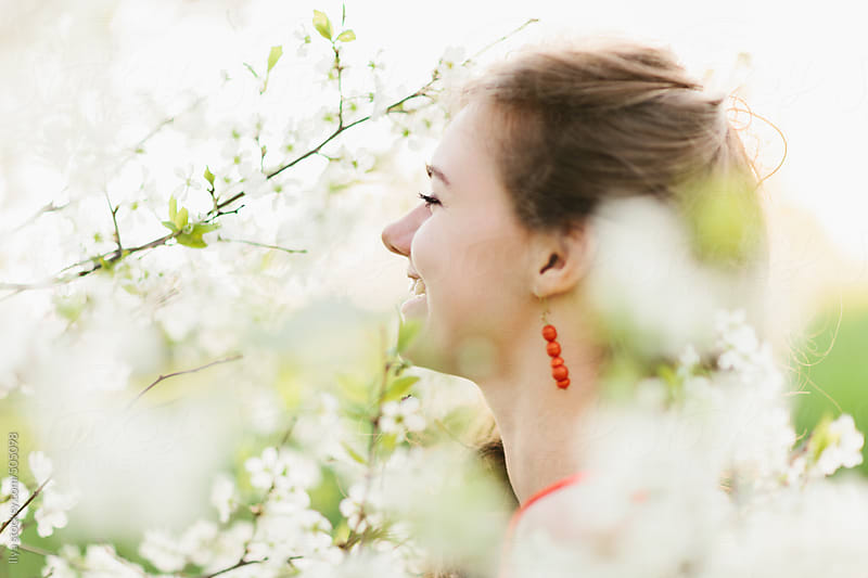 Young woman enjoying apple blooming tree scent by Ilya for Stocksy United