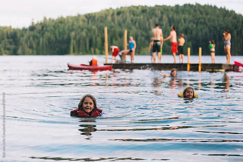 Young girl swimming in lake with lifejacket by Rob and Julia Campbell for Stocksy United